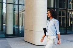 Business professional outside an office building. Walking with digital tablet in her hand stock image