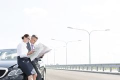 Business professionals analyzing map outside car on road against sky stock images