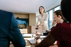 Business professionals brainstorming in office board room. Young people sitting at the table and discussing new projects with female standing Royalty Free Stock Photo
