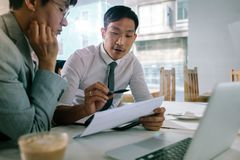Business professionals discussing over some paperwork. Young asian businessman explaining a document to his manager sitting at cafe table. Business professionals royalty free stock photo