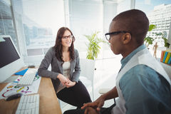 Business professionals discussing while sitting at computer desk Royalty Free Stock Photography