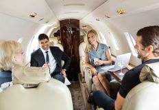Business Professionals Having Drinks On Private. Confident business professionals having drinks on a private jet Royalty Free Stock Photos