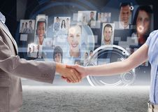Business professionals shaking hands against profile picture interface in background Royalty Free Stock Images