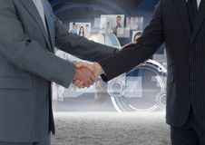 Business professionals shaking hands against technology background Stock Image