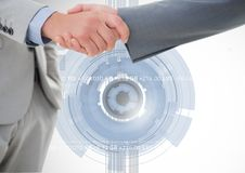 Business professionals shaking hands with handcuff against digital interface in background. Digital composition of business professionals shaking hands against Royalty Free Stock Images