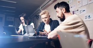 Business professionals at working moments. Group of young confident coworking people analyzing data using computer while royalty free stock photography