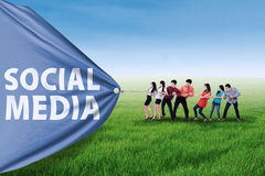 Business promotion with social media banner. Portrait of business team pulling together a banner of social media stock photography