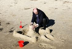 Business protection. Businessman at the beach building a wall around his sandcastle, signifying protecting his business royalty free stock photography