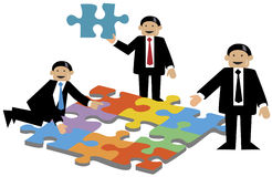 Business Puzzle. Three well dressed business men put puzzles together, one with a puzzle piece in his hand Royalty Free Stock Photos