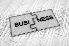 Business puzzle. Two puzzle pieces with the term Business on them over stock charts in the newspaper Stock Image