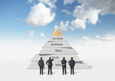 Business pyramid. Businessmans looking at business pyramid Stock Images