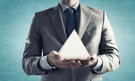 Business pyramid. Close up of businessman holding pyramid in hands Royalty Free Stock Photo