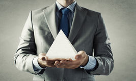 Business pyramid. Close up of businessman holding pyramid in hands Stock Image