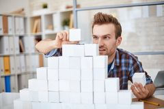 Business pyramid. Creative businessman in casualwear building paper pyramid Stock Images