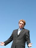 Business Question. Young businessman with arms outstretched, and palms open expresses quizzical look Stock Images
