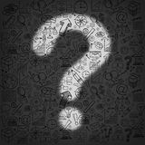 Business Questions. Concept as a dark wall of financial icons and symbols with an illuminated light shaped as a question mark as a metaphor for finding answers Royalty Free Stock Photography