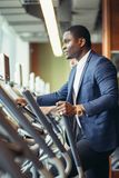 African businessman on the elliptical trainer. Royalty Free Stock Photos