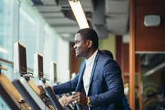 African businessman on the elliptical trainer. Royalty Free Stock Images