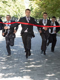 Business race. Business people are crossing red finish tape Stock Photography