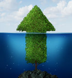 Business Recovery. Concept as an arrow tree drowning underwater emerging to the surface rising out of the ocean as a financial symbol of  economic growth return Royalty Free Stock Images