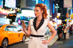 Business red haired woman texting on mobile phone in night New York City street. Portrait of business red haired woman texting on mobile phone in night New York Stock Images