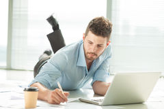 Business report. Businessman working with his report lying on the floor Stock Images