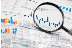 Business report with charts and magnifying glass. Glass business report magnifying computer background money royalty free stock photo