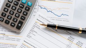 Business report with pen statement with graph. Stock exchange report data number analysis for investment with pen and calculator royalty free stock photos