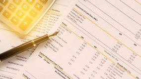Business report with pen statement with graph. Stock exchange report data number analysis for investment with pen and calculator royalty free stock images
