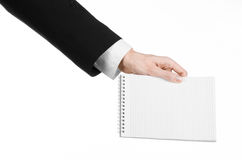 Business and reporter topic: the hand of a journalist in a black suit holding a notebook with a pencil on a white background Royalty Free Stock Images