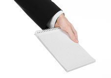 Business and reporter topic: the hand of a journalist in a black suit holding a notebook with a pencil on a white background Royalty Free Stock Photography