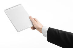 Business and reporter topic: the hand of a journalist in a black suit holding a notebook with a pencil on a white background Stock Photos