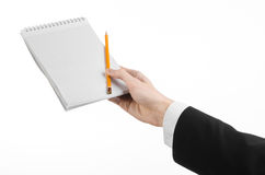 Business and reporter topic: the hand of a journalist in a black suit holding a notebook with a pencil on a white background Stock Image