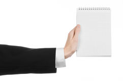 Business and reporter topic: the hand of a journalist in a black suit holding a notebook with a pencil on a white background Stock Photo