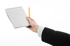 Business and reporter topic: the hand of a journalist in a black suit holding a notebook with a pencil on a white background Royalty Free Stock Image
