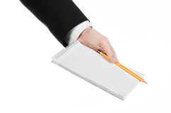 Business and reporter topic: the hand of a journalist in a black suit holding a notebook with a pencil on a white background Stock Images