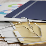 Business reports. And documents, eyeglasses over it, some figures are visible. Shallow DoF Stock Images