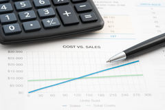 Business reports sales. Business reports cost vs sales, calculator and pen Royalty Free Stock Image