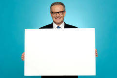 Business representative holding blank ad board. And smiling at camera Royalty Free Stock Photography