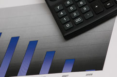 Business results under  scrutiny. Calculator and charts Royalty Free Stock Photos