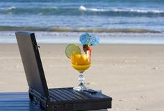 Business reward. Yellow cocktail placed on a laptop, with the beach in the background, signifying reward for hard work completed stock photography