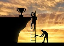 Concept of business success and the envy of rival. A business rival cuts a ladder on which another person climbs to the trophy. The concept of business success Royalty Free Stock Photography