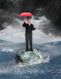 Business Rock Hard Place Despair. A businessman weathers the storm in this metaphor for a bad economy or difficult times in business. The man is stuck in the sea Stock Image