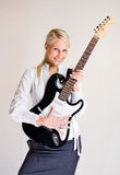 Business is rockin'. Portrait of beautiful young blond business woman with electric guitar Royalty Free Stock Photo