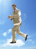 Business running whilst checking wristwatch in mid-air against cloudy sky Stock Images