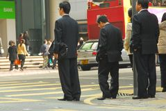 Business Rush Hour. Group of people - including a group of business men - wait for the light to change to cross a busy intersection in Central, Hong Kong Royalty Free Stock Images
