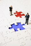 Business sale. Two business man in front on a colored piece of puzzle Stock Images