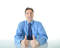 Business or sales man giving two big thumbs up. Business or sales man sitting at desk giving two big enthusiastic thumbs up royalty free stock photo