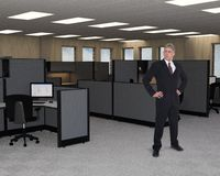 Business Sales Marketing Office, Worker. A businessman stands in a business sales and marketing office with cubicles and workstations. Each workstation Royalty Free Stock Image