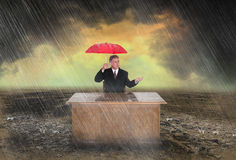 Business Sales Profit Career Marketing. Abstract business concept. A businessman is at his office desk holding an umbrella while sitting in the rain. Metaphor Stock Images